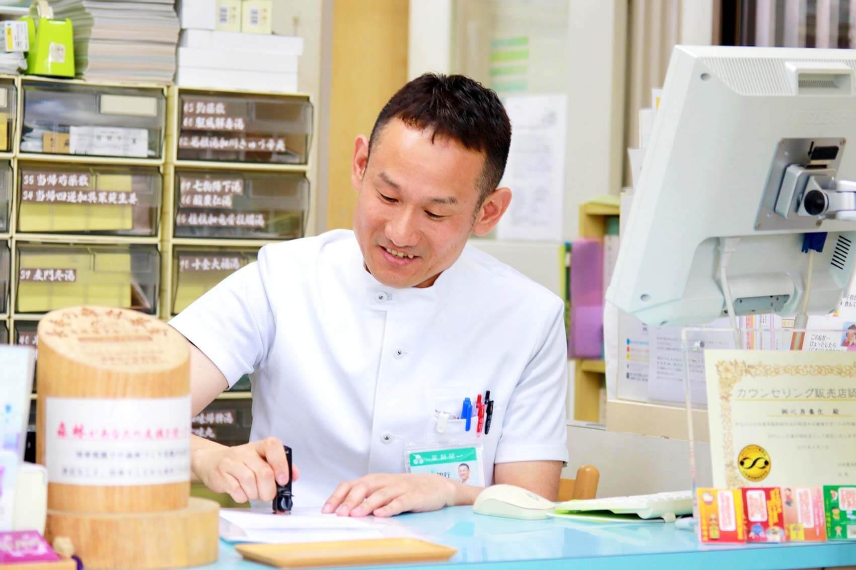 笑顔で患者さんと話す田中局長